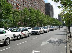 In Madrid taxis are identifiable by their red stripe.